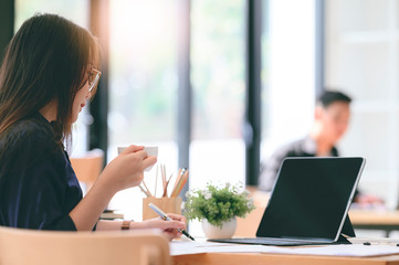 Young woman holding cup of coffee and working with laptop while sitting at table in co-workspace.