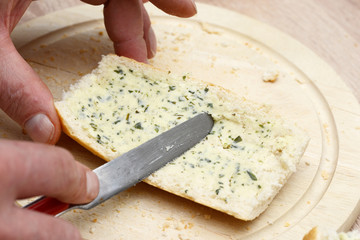 spread rustic crusty white bread with Herb butter in the kitchen