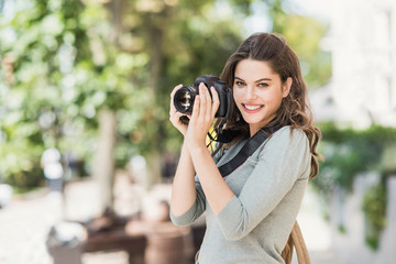Woman professional photographer with dslr camera outdoors portrait.  Pretty young girl in the city taking images with photo camera Fotobehang