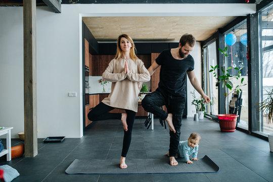 Infant child creeps next to his parents doing yoga