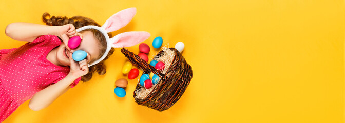 Top view on a happy merry child in bunny ears and a basket with Easter colored eggs. Little girl lies on the floor on a yellow background. Copy space