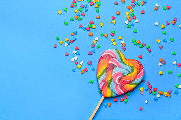 Tasty lollipop with sprinkles on color background