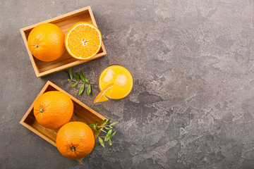 Glass of fresh orange juice and fruit on grunge background