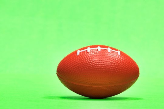 Elongated football sitting at ground level with green background and copy space, Gridiron football season in the USA, ball also represents Aussie Rules and rugby.