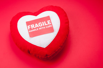 Valentine's Day heart cushion sitting on a bright red background with a Fragile Handle With Care Sticker