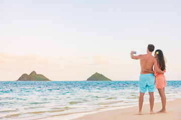 Beach vacation tourists couple taking picture with phone of Hawaii islands. Honeymoon summer travel holidays.