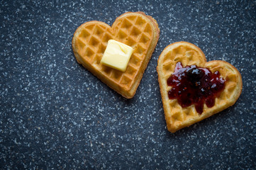 Pair of love heart-shaped waffles topped with berry jam and butter on a grey stone background