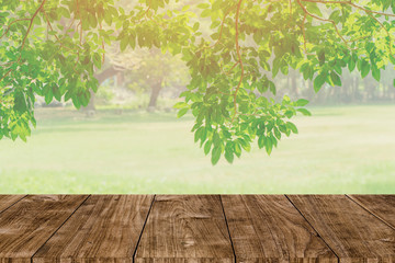 Wood table top on blur abstract green tree garden in the morning background. nature park for montage product display or design key visual layout