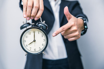 business people hand finger pointing at clock times at 8 o'clock, reminder time to do something or timing notice concept