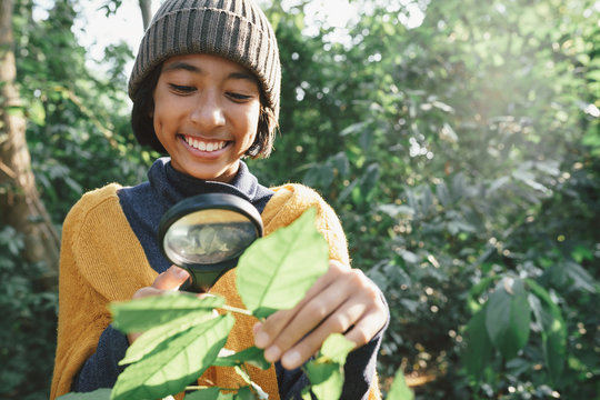 Asian little girl exploring the nature with magnifying glass and happy smile In the midst sunlight in the morning