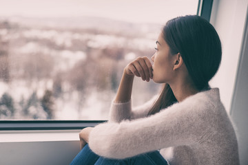 Winter depression - seasonal affective disorder mental health woman sad comtemplative looking out the window alone.
