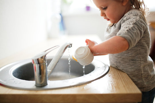 Toddler child washes dishes in sink