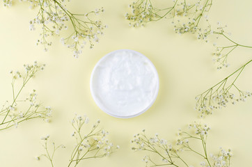 Jar of cream on a light background with small white flowers.