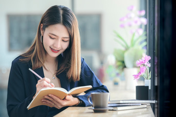 Shot of young asian woman using pencil writing on notebook while sitting at cafe.