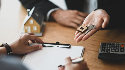 Cropped shot of Real estate agent giving a property key to his customer while signing an agreement on clipboard at the modern wooden table. Realtor/Broker/Seller/Dealer concept.