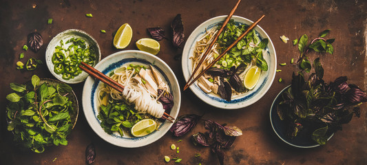 Asian cuisine lunch. Flat-lay of Vietnamese rice noodle chicken soup Pho Ga with fresh cilantro, soy sprouts, greens, lime in bowls with chopsticks over rusty dark background, top view. Healthy food