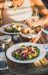 Young woman eating salad with seafood and drinking wine in summer open-air cafe in Italy with picturesque sea view background, selective focus. Travel, wanderlust, Italian lifestyle concept