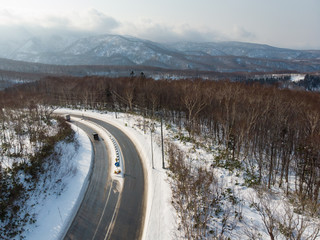 Oblique view of a road with a truck and car on it that curves around a mountain slope in a early winter morning where there is sunlight falling on freshly fallen snow