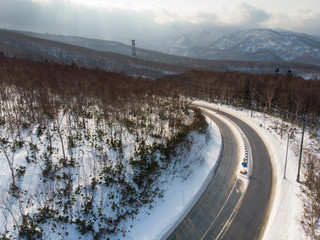 Oblique view of a road with a truck and car on it that curves around a mountain slope in a early winter morning where there is sunlight that shine through from clouds falling on freshly fallen snow