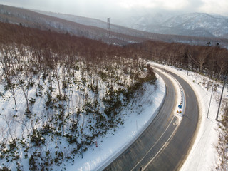 Oblique view of an empty road that curves around a mountain slope in a early winter morning where there is sunlight falling on freshly fallen snow