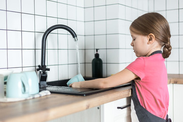 A cute little European girl washes dishes in an apron in the bright kitchen. The child helps in the kitchen to wash and wipe dishes.