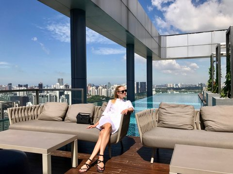 Woman in white dress with sunglasses sitting in lounge on rooftop before pool, Singapore, South East Asia