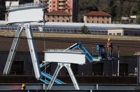 Builders work on the construction of the new Genoa bridge, also known as the Polcevera viaduct