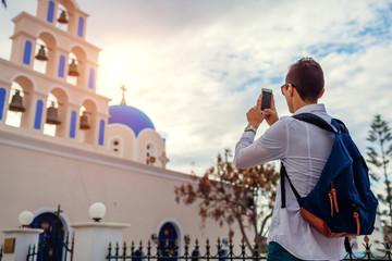 Santorini traveler taking photo of church in Akrotiri on smartphone. Tourism, traveling, vacation concept