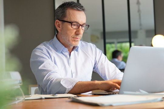 Business manager working in office on laptop