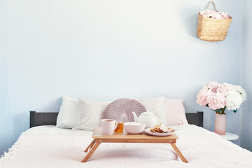 Breakfast in bed in hotel room. Accommodation. Breakfast in bed with tea cup with pancakes on tray on bed background top view. Copy Space. Romantic valentine's day breakfast. Cozy breakfast Maslenitsa