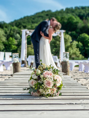 Wedding bouquet in front of newlyweds wedding couple inbackground, kissing or holding hands in love Shallow depth bokeh