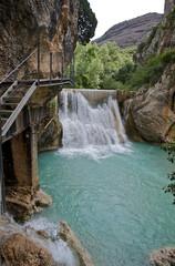Pequeña cascada de un río con el agua color turquesa