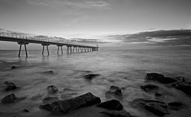 Puente en medio del mar con un faro al final en blanco y negro