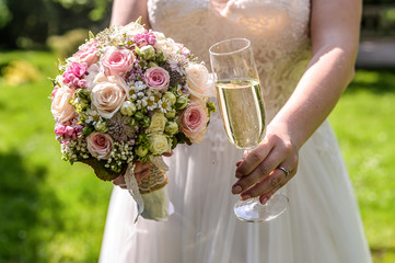 Bride holding bouquet of flowers and a glass of sparkling wine closeup wedding marriage