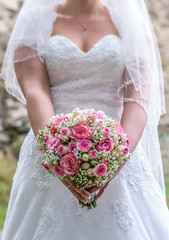 Wedding bouquet of flowers held by bride closeup. Pink flower