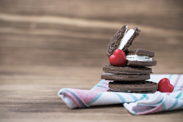 chocolate cookie sandwich on a colored napkin on a wooden background. wooden and red hearts. happy Valentine's day. beautiful picture with biscuits. texture.