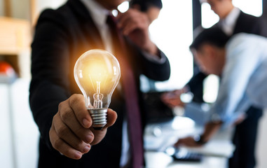 Innovation and idea of professional leader holding lighting bulb, business people planing and analysis work on table in office, brainstorming teamwork and thinking management concept