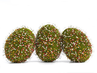 Three Easter eggs covered with grass and spring flowers