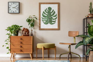 Vintage interior design of living room with design retro furnitures, plants, shelf, black clock and brown poster mock up frame on the beige wall. Stylish home decor. Template.