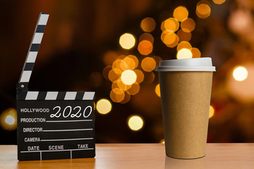 Takeaway coffee in a paper cup dark background, Clapperboard
