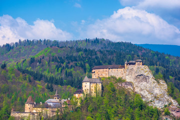orava castle of slovakia. medieval fortress on a hill in a beautiful place in mountains. wonderful sunny weather with fluffy clouds in springtime
