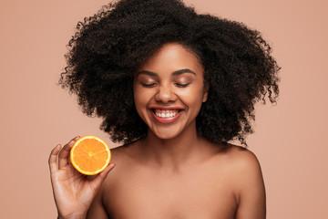 Cheerful African woman with ripe orange