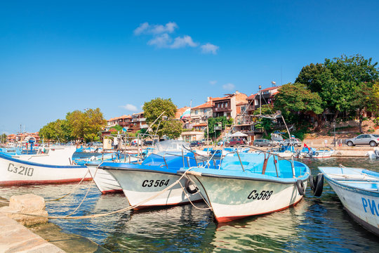 sozopol, bulgaria - SEP 09, 2019: fishing boats in port on a sunny day. embankment on the background of a scenery. reflection on the water