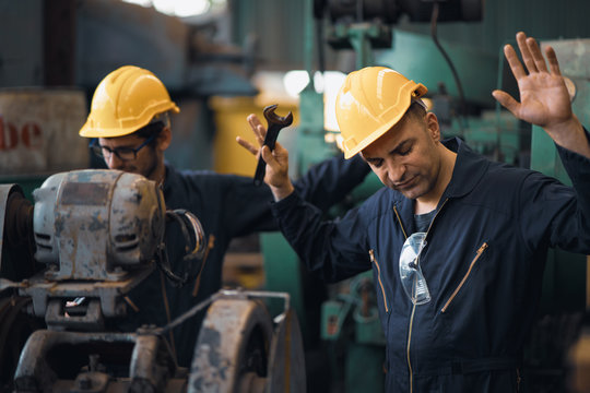 Shot of two industrial workers feeling bad with old system in the factory, the worker feels upset and show give up, Concept industrial workers with bad emotion when working time, working confliction.