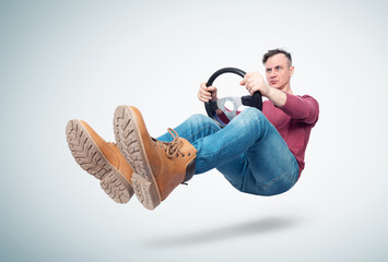 Man in jeans and red t-shirt drives a car with a steering wheel, on light background. Auto driver concept