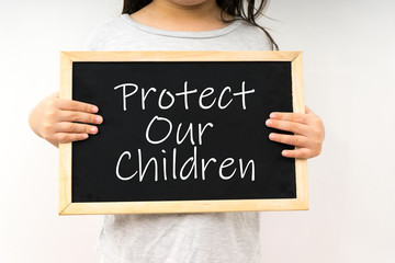Young girl hold a chalkboard with text protect our children.