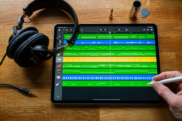 BATH, UK - FEBRUARY 10, 2020: Garage Band application being used to create and arrange music  on an Apple iPad Pro in a home studio environment.