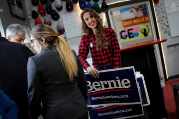 Colleen Jackson hands out yard signs for Democratic U.S. presidential candidate Senator Bernie Sanders at a breakfast campaign stop in Manchester