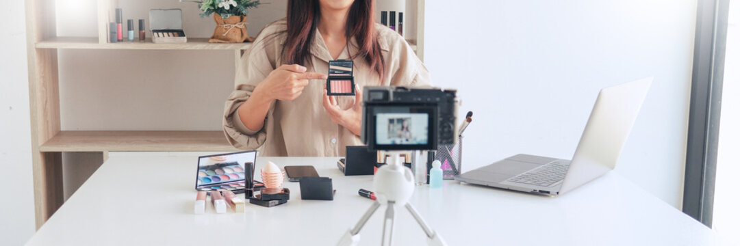 beautiful asian woman professional beauty vlog or blogger present cosmetics and applying make-up in front camera for recording video.