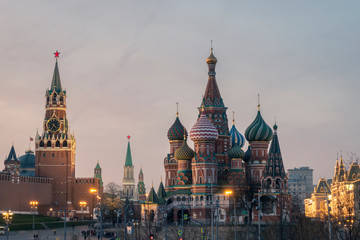 Poster Moscow Spasskaya tower with watch of Moscow Kremlin architectural ensemble and Saint Basil's Cathedral at night.